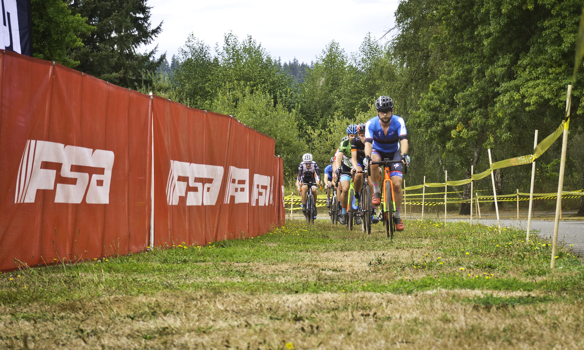 Cyclocross racers on grass course